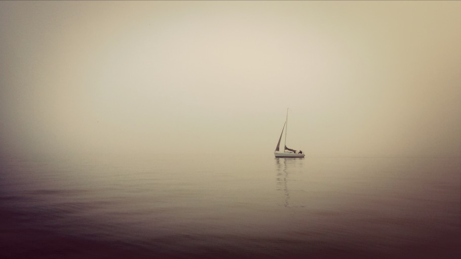 Sailboat in still water with mist