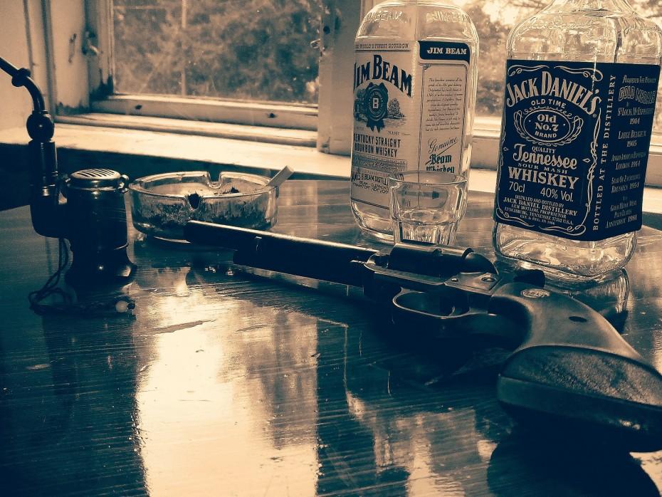 Pöydällä Viskipullo ja Revolveri